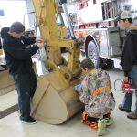 Local Hastings students inspect and grease a 315d excavator